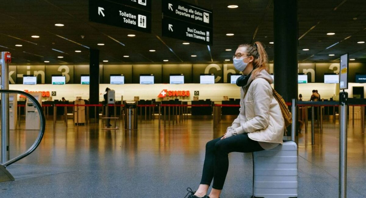 girl sitting on suitcase at airport wearing mask